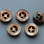 Brown MOP shell buttons with logo carved